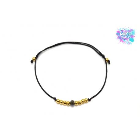 Goldenes Perlenarmband mit schwarzer facettierten Perle